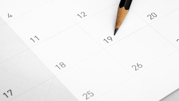 Het potlood wijst naar de negentien in de kalender