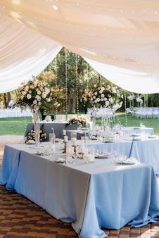Het presidium van de pasgetrouwden in de feestzaal van het restaurant is versierd met kaarsen en groene planten, blauweregen hangt aan het plafond