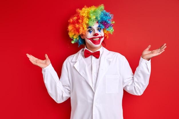 Het presteren van de harlekijn, clown die met gelukkig gezicht glimlacht dat witte uitrusting en geschilderd gezicht op rode achtergrond draagt