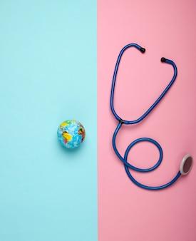 Het probleem van de wereldwijde pandemie. stethoscoop en globe op roze blauwe muur wereldwijde epidemie. bovenaanzicht