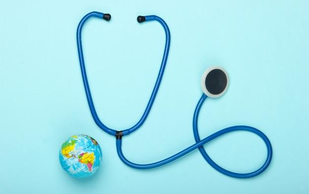 Het probleem van de wereldwijde pandemie. stethoscoop en wereldbol op een blauwe muur wereldwijde epidemie. bovenaanzicht