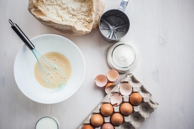 Het proces om het deeg te maken, de hand van de vrouw zwepen eieren en bloem in kom