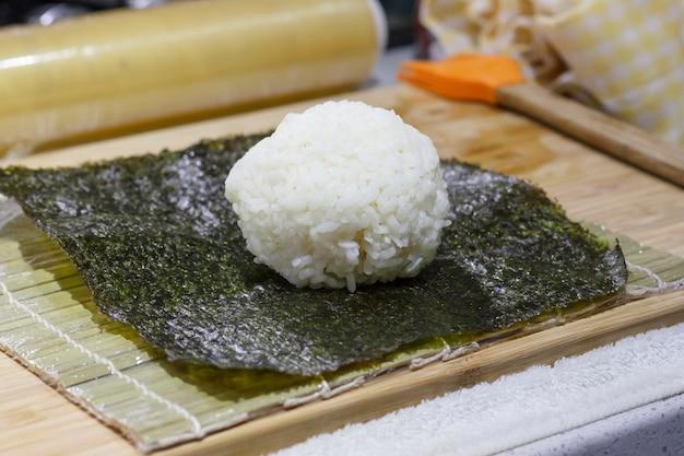 Het proces om sushi en broodjes te maken met komkommer. rijst op nori-blad