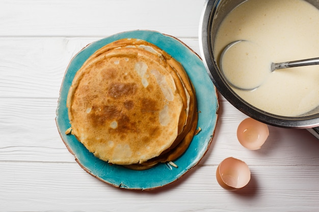 Het proces om traditionele dunne pannekoeken te maken. pannenkoeken en een kom met een test op de tafel.