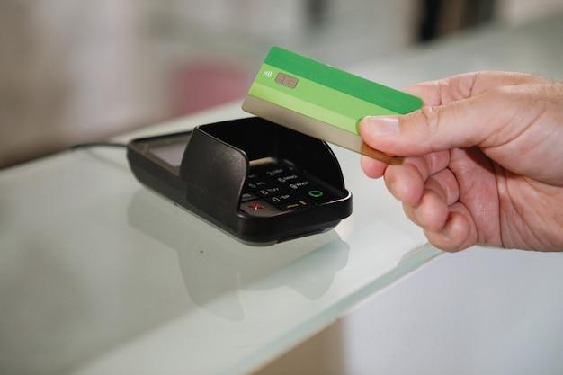 Het proces van betalen met een contactloze bankkaart met een plastic kaart in de winkelterminal.