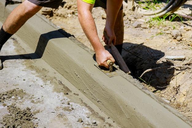 Het proces van de constructie van de stoep, de installatie van een betonnen stoeprand in aanbouw