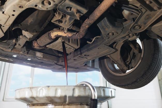 Het proces van het aftappen van gebruikte motorolie uit het carter in het carter