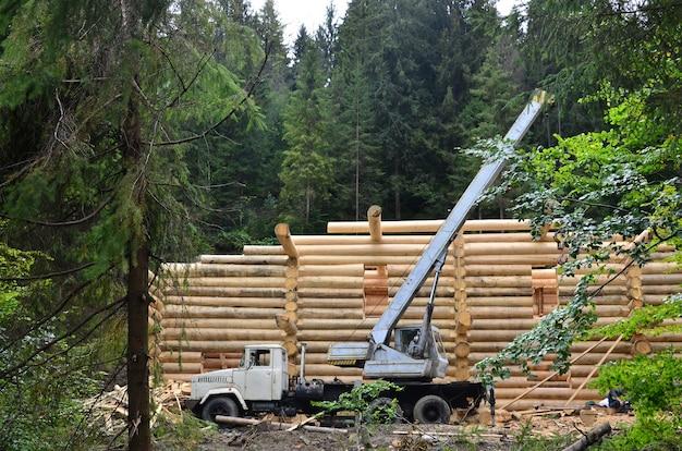 Het proces van het bouwen van een houten huis uit houten balken van cilindrische vorm. kraan in werkende staat