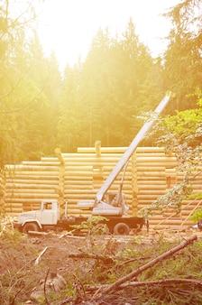 Het proces van het bouwen van een houten huis uit houten balken van cilindrische vorm.