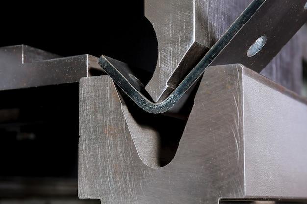 Het proces van het buigen van plaatwerk op een hydraulische buigmachine. metaalbewerkingsfabriek. Premium Foto