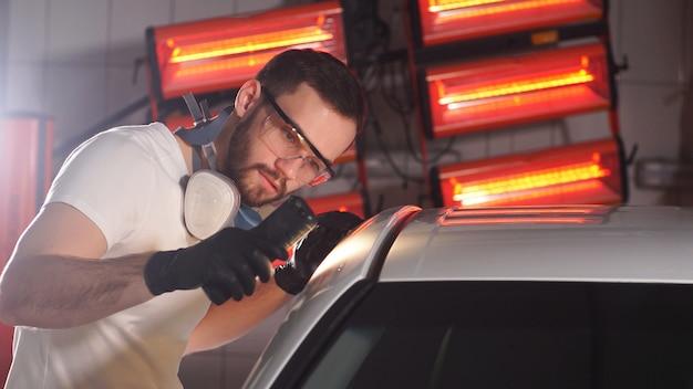 Het proces van het controleren van de toepassing van nanokeramische coating op een auto door een mannelijke werknemer met behulp van een zaklamp