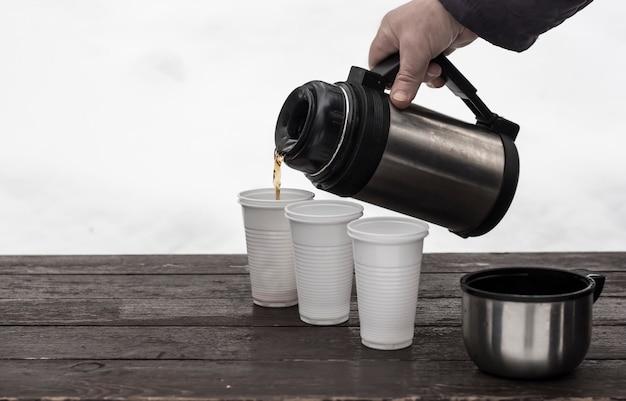 Het proces van het gieten van koffie in wegwerpglazen in de winter in de natuur.