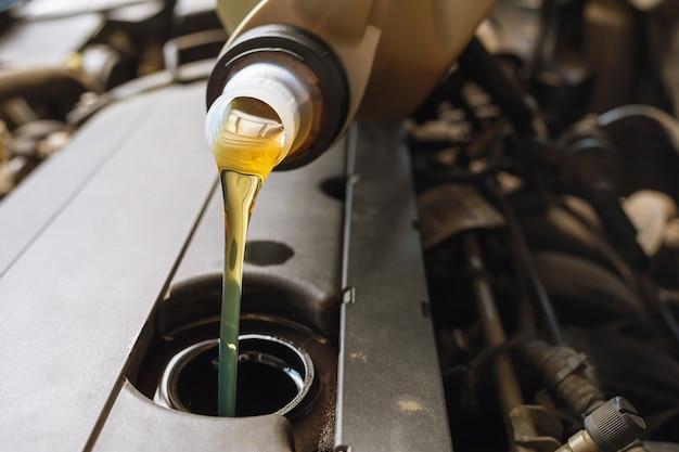 Het proces van het gieten van motorolie in de close-up van de motor