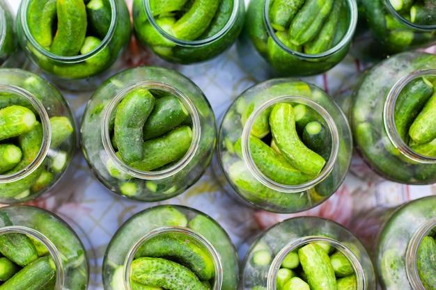 Het proces van het inblikken van ingelegde augurken voor de winter, augurken komkommers in glazen potten close-up
