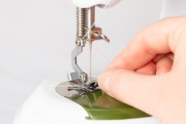 Het proces van het inrijgen van de draad in het oog van de naald van een naaimachine