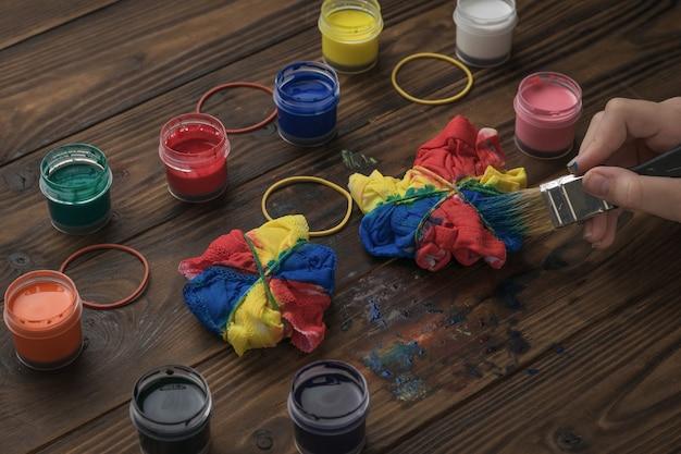 Het proces van het kleuren van witte kleding in de stijl van stropdaskleurstof thuis. stof beitsen in tie-dye-stijl.