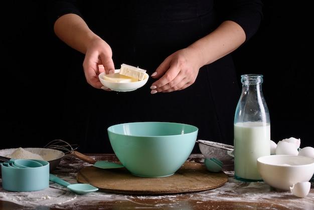 Het proces van het maken van cupcakes, het coaten van een crème uit een spuitzak in de handen van een banketbakker.