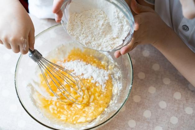 Het proces van het maken van deeg voor pannenkoeken met ingrediënten op een lichte tafel, eieren en meel wordt opgeklopt met een mixer