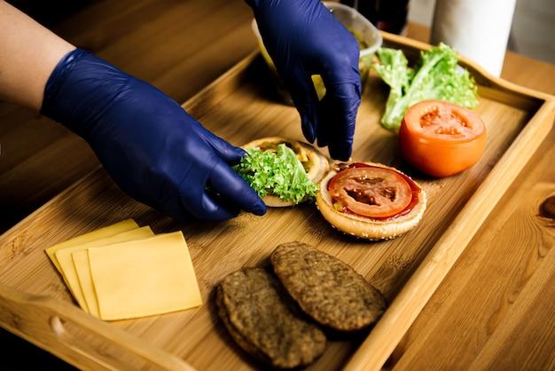 Het proces van het maken van een cheeseburger op een houten tafel