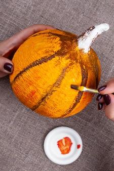 Het proces van het maken van een pompoen van papier-maché voor halloween-decor, tekenen met verf, close-up.