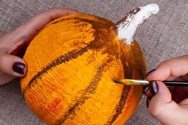 Het proces van het maken van een pompoen van papier-maché voor halloween-decor, tekenen met verf, handen met een penseel.