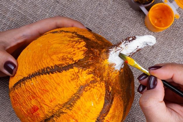Het proces van het maken van een pompoen van papier-maché voor halloween-decor, tekenen met verf