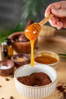 Het proces van het maken van een zelfgemaakte koffiescrub voor huidverzorging met het toevoegen van honing milieuvriendelijke cosmetica