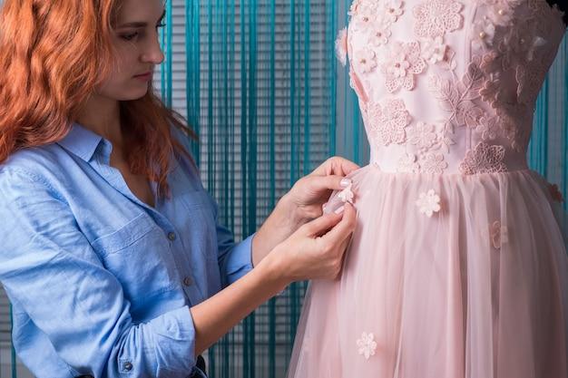 Het proces van het maken van kleding. professionele ontwerper, handgemaakte vakman, naait bloemen op een roze jurk, op een paspop, in een werkplaats. maatwerk, dameskleding. roze trouwjurk