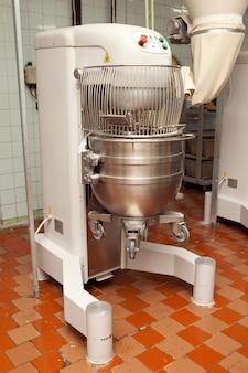 Het proces van het maken van koekjesdeeg in een industriële kneedmachine in de fabriek.