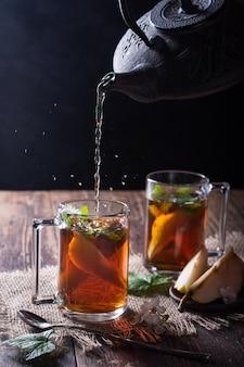 Het proces van het maken van thee, theeceremonie, een kopje vers gezette zwarte thee met plakjes peer en zwarte bessenbladeren