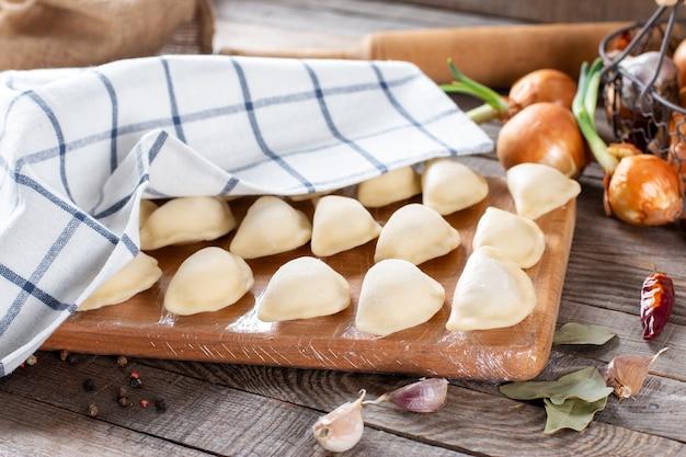 Het proces van het maken van zelfgemaakte dumplings. knoedels vormen. ruwe zelfgemaakte dumplings op een houten bord.