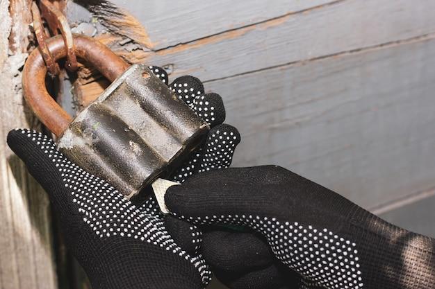 Het proces van het openen van een oud slot oud hangslot gehandschoende handen openen het slot