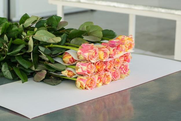 Het proces van het verpakken van bloemen met papier, voorbereiding voor transport