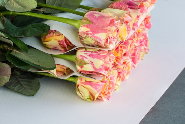 Het proces van het verpakken van rozenbloemen met papier, voorbereiding voor transport
