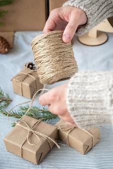 Het proces van het verpakken van stijlvolle, moderne cadeaus voor kerstmis en nieuwjaar. geschenkdoosjes van kraftpapier, touw en kerstboomtakken. kerst achtergrond, vakantie sfeer.