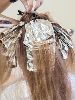 Het proces van het verven van haar. folie op het haar bij het kleuren van het haar.