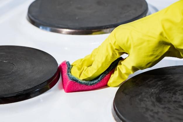 Het proces van het wassen van een elektrisch fornuis. een hand in een gele handschoen reinigt het witte oppervlak van vuil.