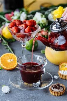 Het proces van het zetten van natuurlijke thee met aardbeien, theeceremonie. een kopje vers gezette fruitthee. hete thee wordt in een glazen beker op een decoratieve tafel gegoten