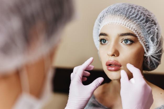 Het proces van lippenverbetering. de dokter beoordeelt verbeterde lippen. het jonge meisje met een mooi gezicht in speciale hoed en de handen van de dokter in roze handschoenen.