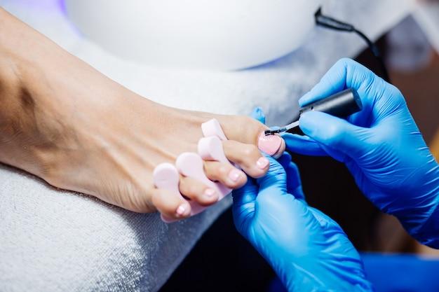 Het proces van professionele pedicure met meester in blauwe handschoenen die lichtroze gelpoets toepassen
