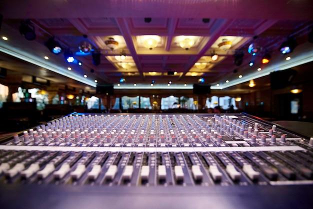 Het professionele controlebord van dj op een vage feestelijke zaal als achtergrond.