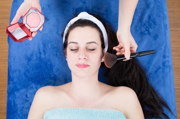 Het professionele make-upkunstenaar van toepassing zijn bloost aan vrij donkerbruine vrouw