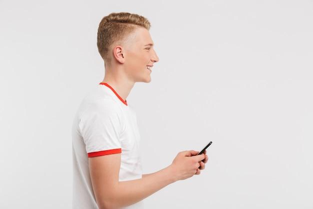 Het profiel stelde tiener tevreden die vrijetijdskleding dragen die en internet op celtelefoon typen doorbladeren op wit wordt geïsoleerd