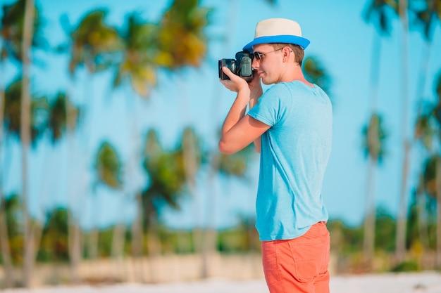 Het profiel van de jonge mens fotografeerde mooi zeegezicht op wit zandstrand
