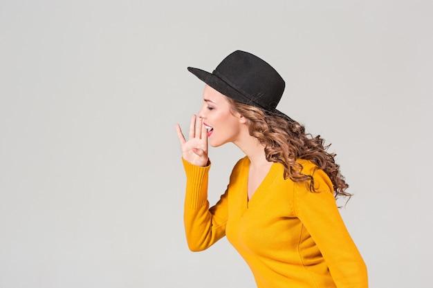 Het profiel van emotioneel meisje in hoed op grijs