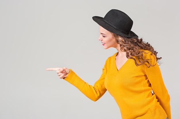 Het profiel van emotioneel meisje in hoed op grijze muur