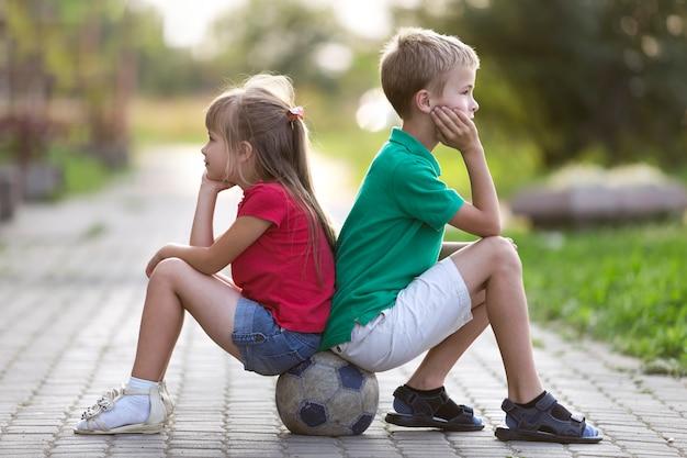 Het profielportret van twee leuke blonde kinderen, glimlachende jongen en langharige meisjeszitting op voetbalbal op lege zonnige voorstad bedekte weg vertroebelde de heldere zomer. kinderspellen en leuk concept.