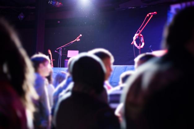 Het publiek bij het podium wacht op de artiest.