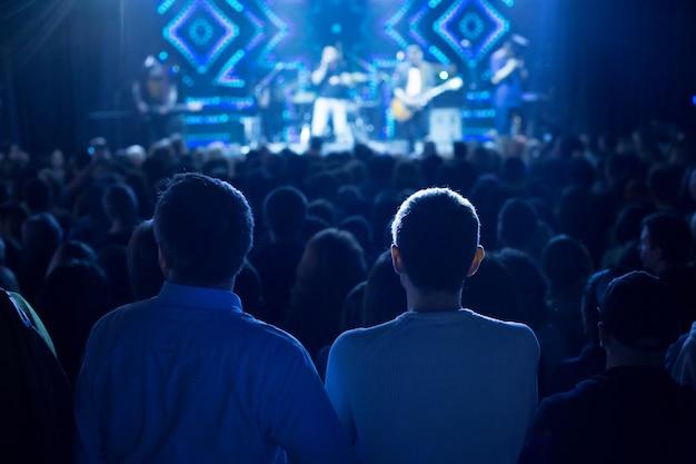 Het publiek kijkt naar het concert op het podium.