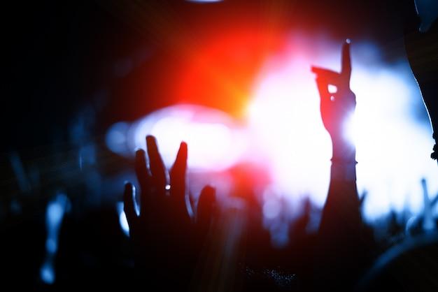 Het publiek van de silhouetmenigte in overleg met handen heft op muziekfestival en kleurrijk verlichtingsstadium op